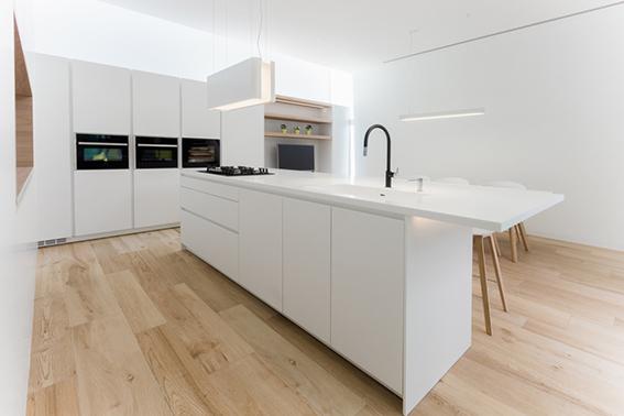 Cocina panelada blanca con isla con zona de cocción y fregadero. Suelo madera clara