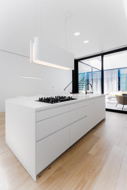 Detalle iluminación y módulos de isla con zona de coción en cocina