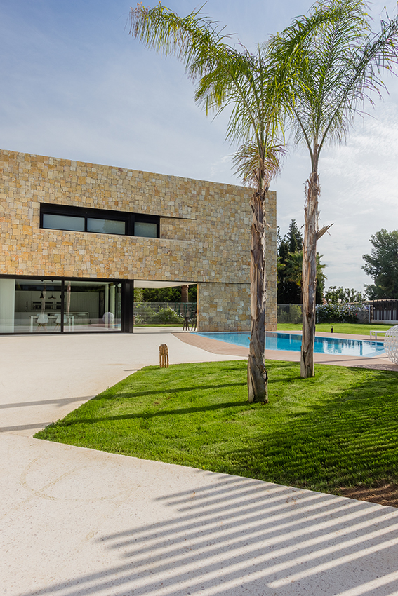 Foto vertical vista piscina frente a fachada de piedra. Arquitectura contemporánea